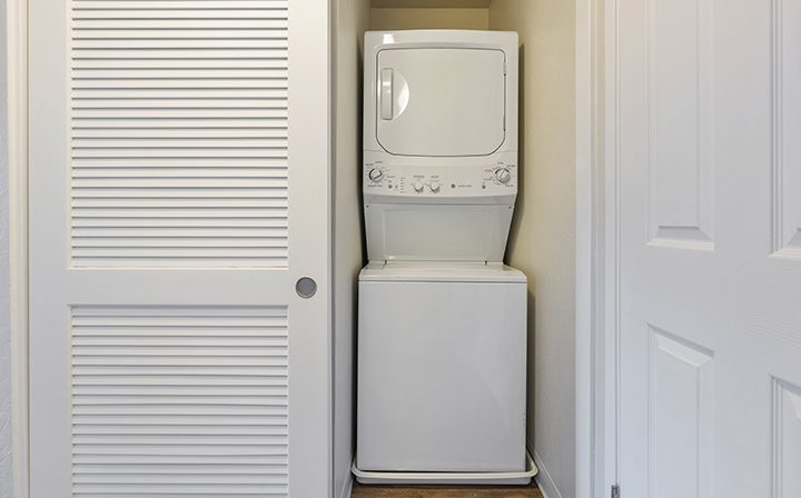 Hallway closet with washer/dryer combo at Mountain View apartments community Highland Gardens