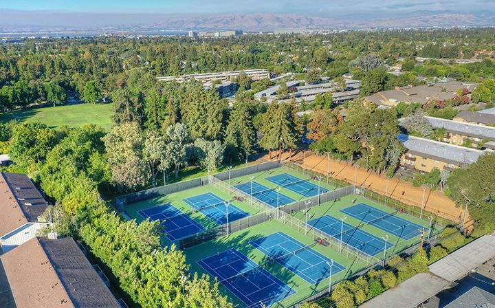 Aerial view of several tennis courts by the Highland Gardens Mountain View apartments