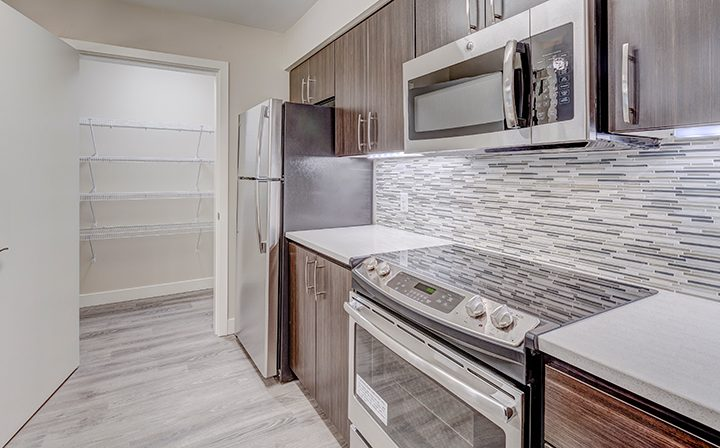 Kitchen with walk-in pantry and microwave over stove at Kent apartments community Indigo Springs
