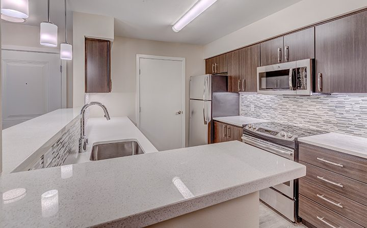White kitchen countertops and brown cabinets over stove at Kent apartments community Indigo Springs