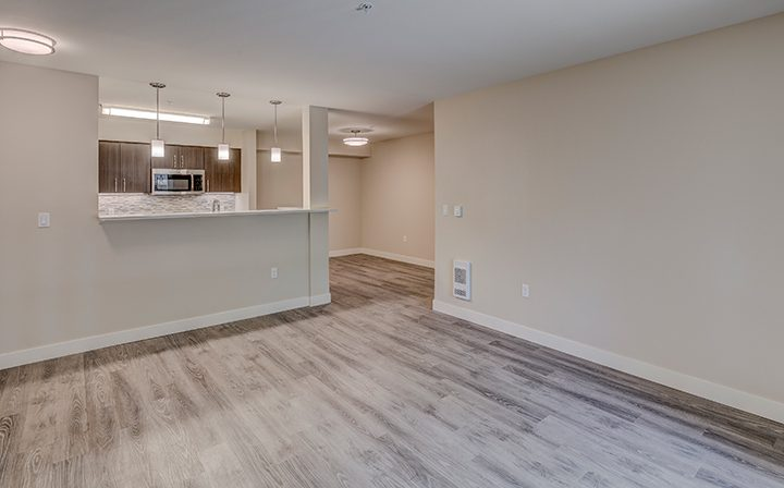 Large unfurnished living room and kitchen with hardwood floors at Indigo Springs apartments in Kent