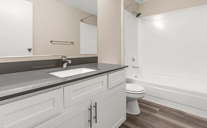 Unfurnished bathroom with inset shower / bathtub combo at Kent apartments community Indigo Springs