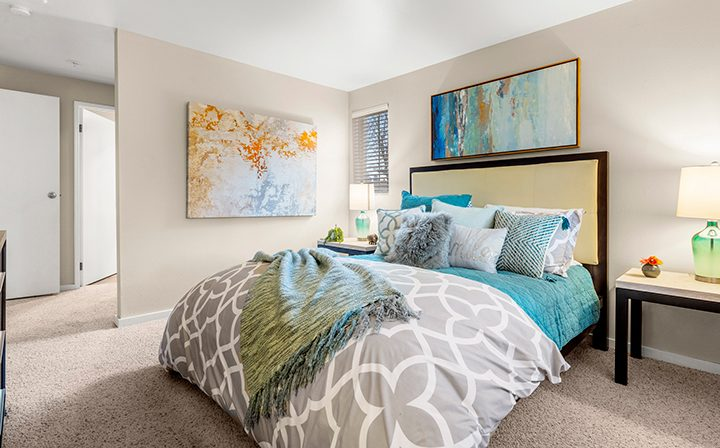 Cozily decorated bedroom with carpet floor and wall art at Kent apartments community Indigo Springs