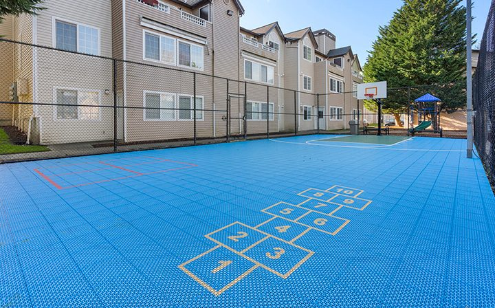 Blue basketball court with hopscotch area at Kent, Washington apartments at Indigo Springs