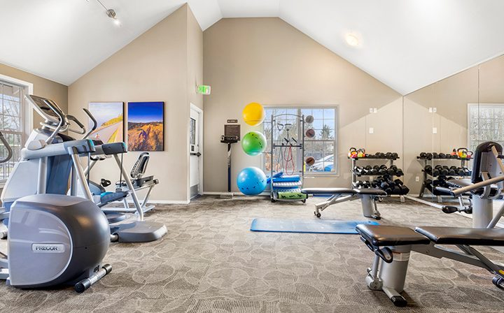 Well-lit fitness center with free weights and arched ceiling at Indigo Springs apartments in Kent