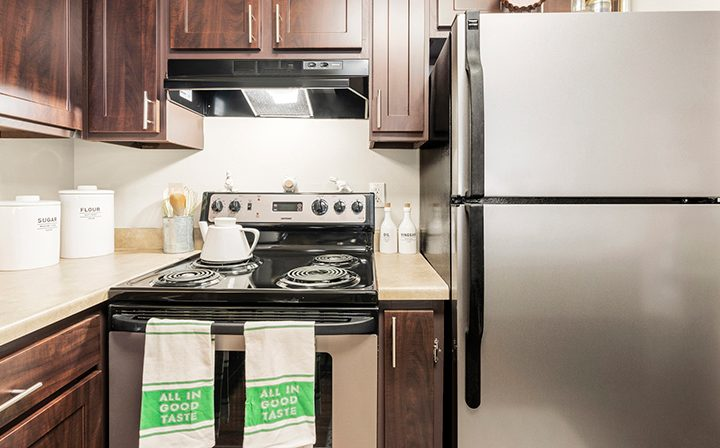 Furnished kitchen with brown cabinets and electric stove at Indigo Springs apartments in Kent