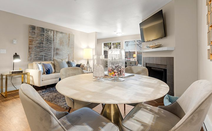 Cream table, chairs, and walls in furnished living room at Kent apartments community Indigo Springs
