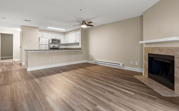 Unfurnished living room and kitchen with fireplace at Indigo Springs apartments in Kent, WA