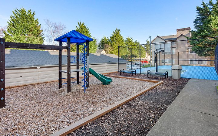 Playground with monkey bars and slide next to basketball court at Kent apartments at Indigo Springs