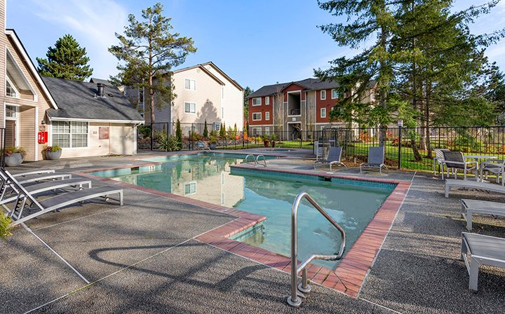 Angular pool with red brick trim next to grassy grounds at Kent apartments community Indigo Springs