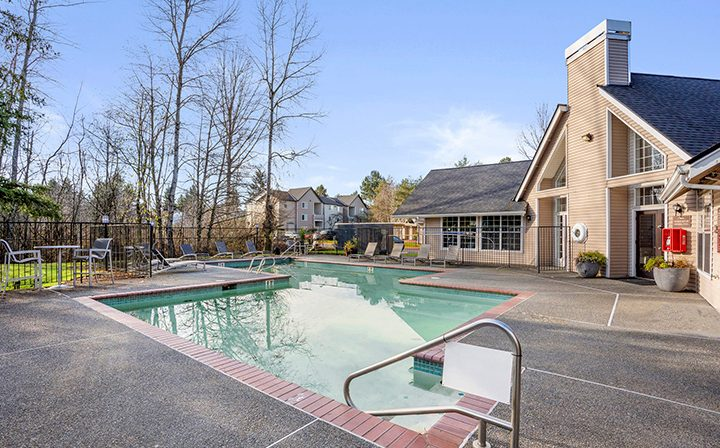 Pool with red brick trim next to grassy grounds at Indigo Springs, a Kent apartments community