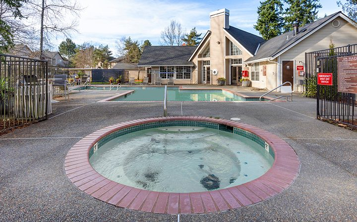 Circular hot tub spa next to pool on cloudy day at Indigo Springs, a Kent apartments community