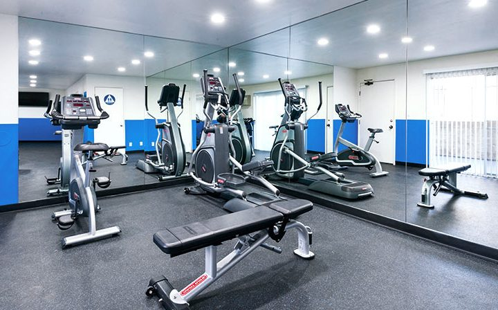 Fitness center with machines and mirrored wall at the Los Angeles apartments community Kaitlin Court
