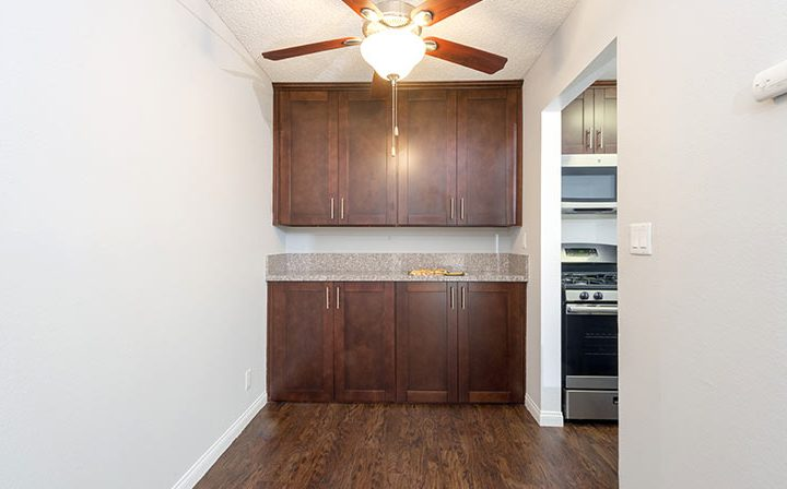 Cabinets under counter next to kitchen nook at the Los Angeles apartments community Kaitlin Court