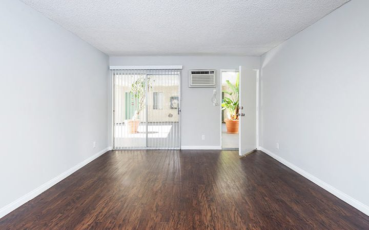 Sunny unit interior with tall windows by door at the Los Angeles apartments community Kaitlin Court