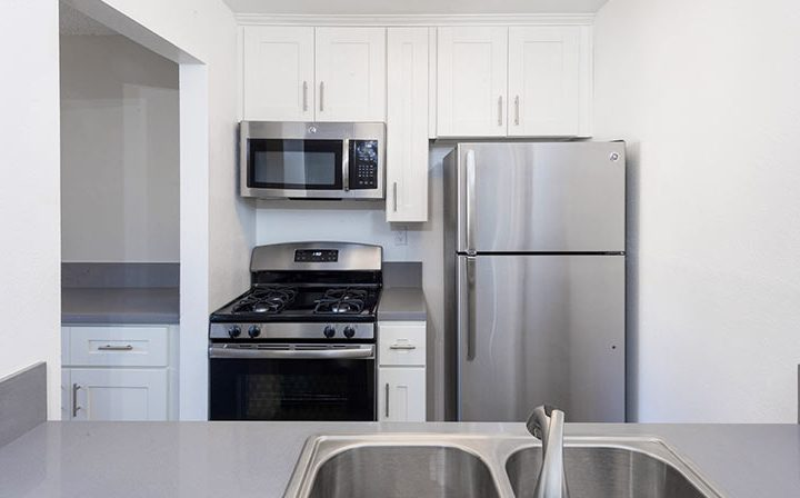 Sink facing fridge and range in kitchen nook at the Los Angeles apartments community Kaitlin Court