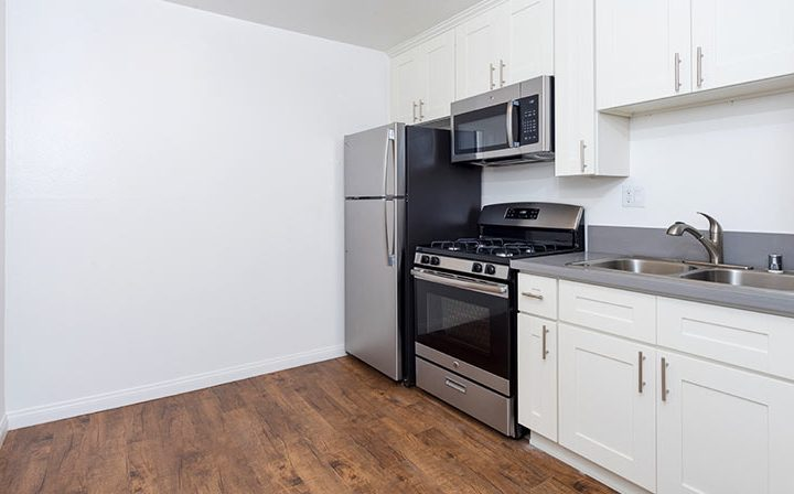 Fridge, range, and sink in unfurnished kitchen at Kaitlin Court, apartments in Los Angeles