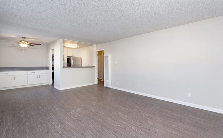 Unfurnished living room with kitchen nook at the Los Angeles apartments community Kaitlin Court