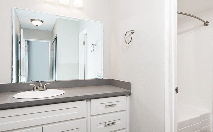 White cabinets in unfurnished bathroom at Kaitlin Court, apartments in Los Angeles