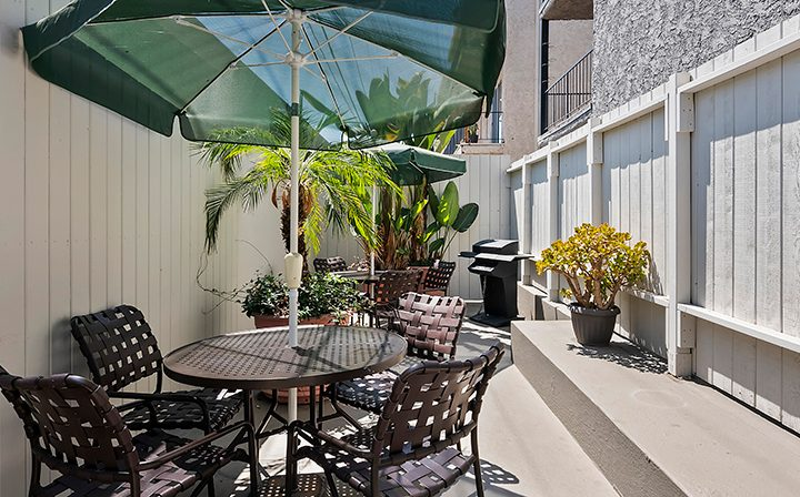 Outdoor seating area with green umbrella at the Los Angeles apartments community Kaitlin Court