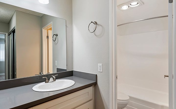 Sink and mirror next to shower/tub combo at the Los Angeles apartments community Kaitlin Court