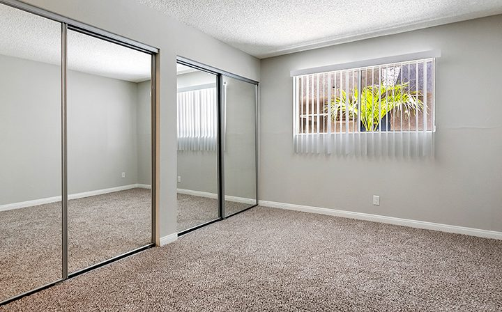 Carpeted bedroom with mirrored closet at the Los Angeles apartments community Kaitlin Court