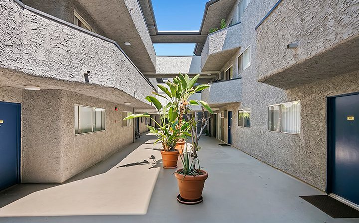 Adjacent blue doors to units in outdoor courtyard at Kaitlin Court, apartments in Los Angeles