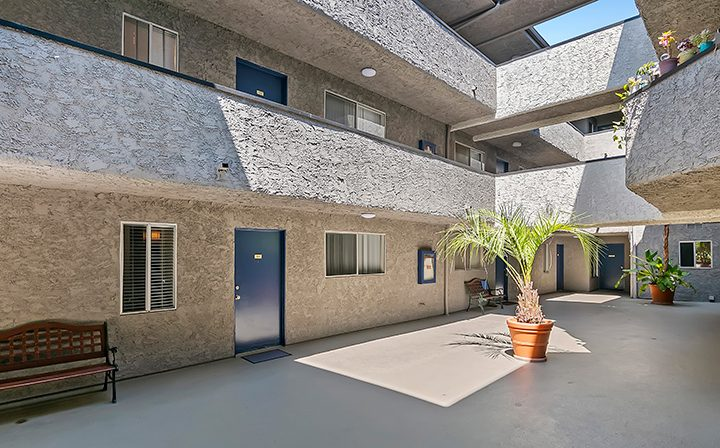Courtyard outside units with potted plants at the Los Angeles apartments community Kaitlin Court