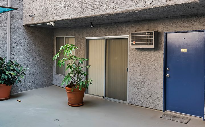 Exterior view of entrance to a unit next to potted plant at Kaitlin Court, apartments in Los Angeles