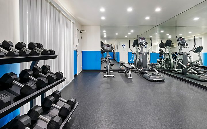 Weights and machines in fitness center with blue accents at Kaitlin Court, apartments in Los Angeles