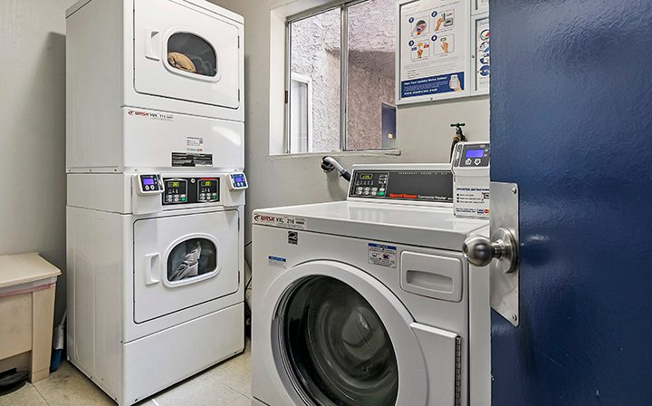 Laundry room with card-operated washers and dryers at Kaitlin Court, apartments in Los Angeles