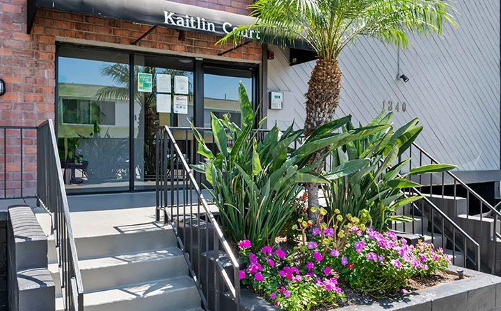 Entrance to Kaitlin Court, apartments in Los Angeles, with stairs and planter outside brick building