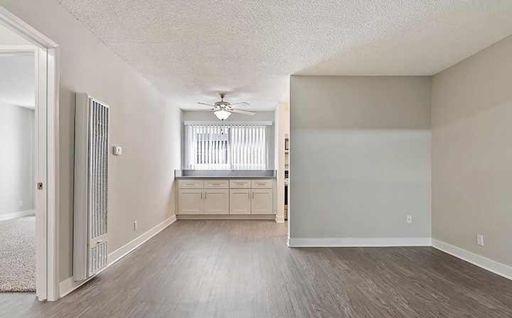 Well-lit unfurnished living room with wood floors at Kaitlin Court, apartments in Los Angeles