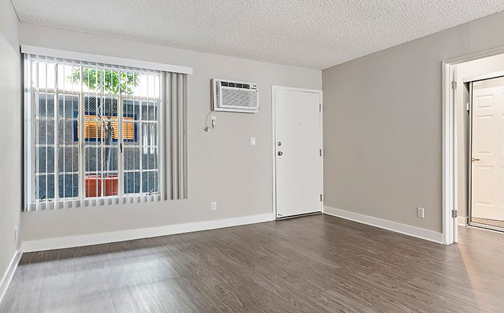 Sunny, unfurnished living room by door at the Los Angeles apartments community Kaitlin Court