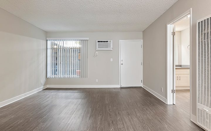 Unfurnished living room with wood floors facing door at Kaitlin Court, apartments in Los Angeles