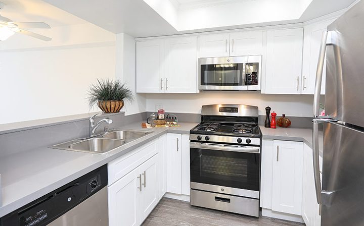 Furnished kitchen with white cabinets at Kingsley Drive, apartments in Koreatown, Los Angeles