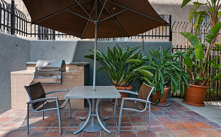 Shaded seating area next to BBQ grill at Kingsley Drive, apartments in Koreatown, Los Angeles
