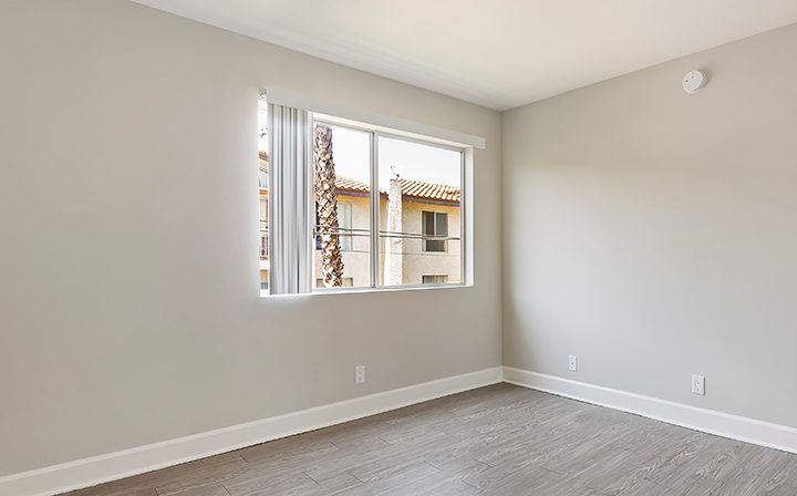 Sunny bedroom with wood floor at the Koreatown apartments community Kingsley Drive in Los Angeles