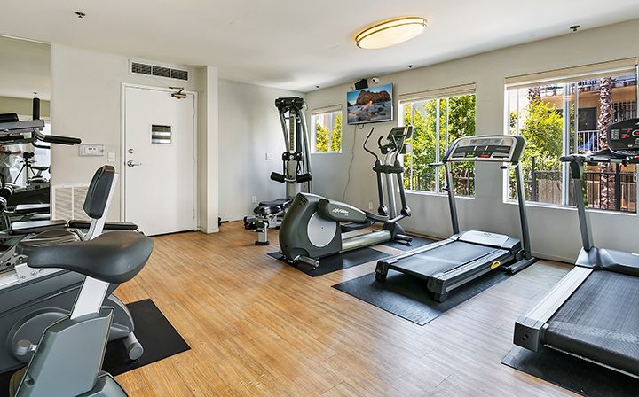 Fitness center with machines at the Koreatown apartments community Kingsley Drive in Los Angeles