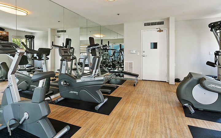Machines and mirrored wall in fitness center at Kingsley Drive, apartments in Koreatown, Los Angeles