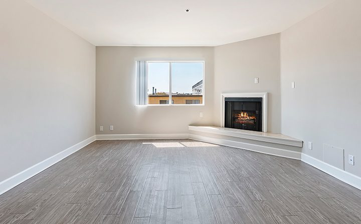 Living room with fireplace at the Koreatown apartments community Kingsley Drive in Los Angeles