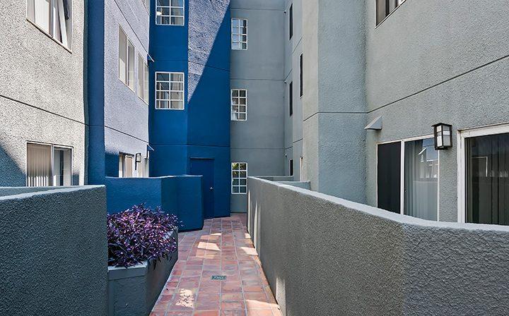 Narrow outdoor courtyard walkway at Kingsley Drive, apartments in Koreatown, Los Angeles