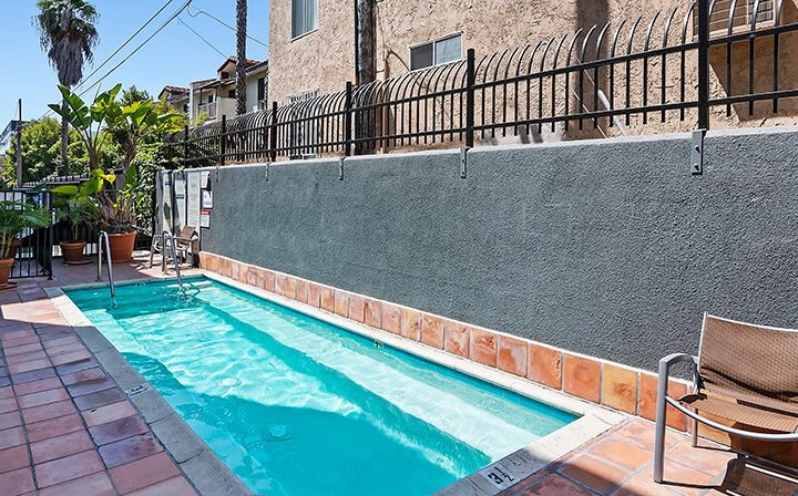 Long and narrow outdoor pool at the Koreatown apartments community Kingsley Drive in Los Angeles