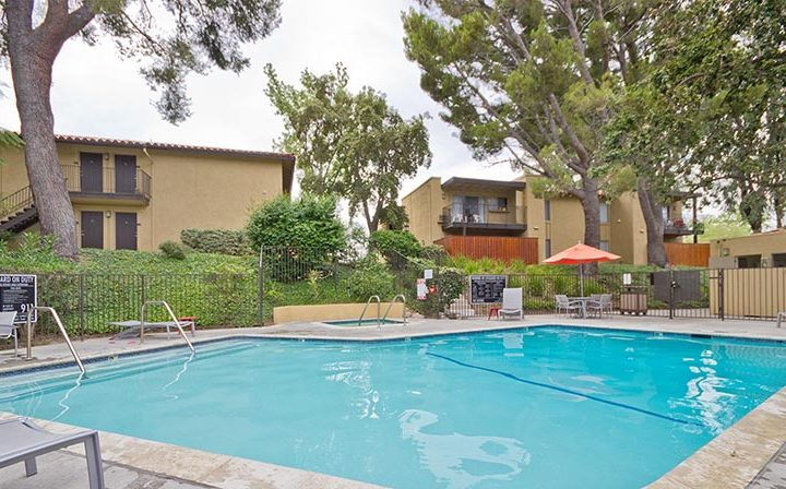 Pool next to chairs under orange umbrella at the Thousand Oaks apartments community Los Robles
