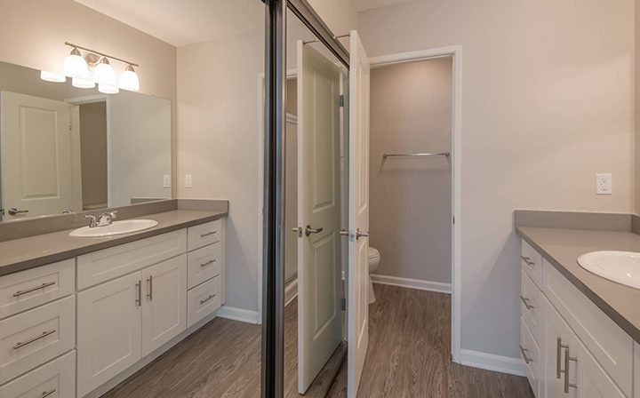 Unfurnished bathroom with vanity and mirrored closet at Los Robles, apartments in Thousand Oaks