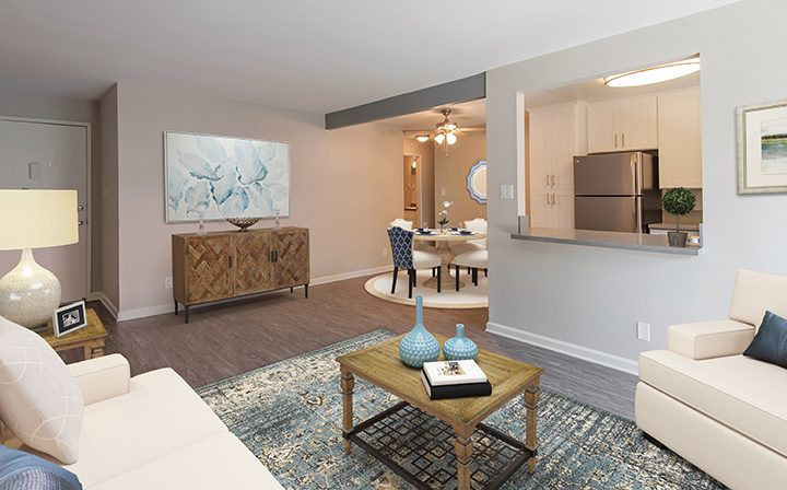 Render of furnished living room with kitchen at the Thousand Oaks apartments community Los Robles