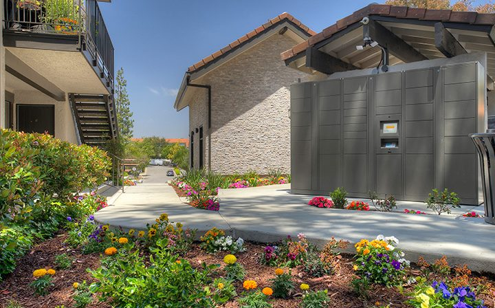 Landscaped plants by cement pathway between units at Los Robles, apartments in Thousand Oaks