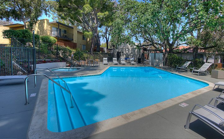 Pool next to chairs at the Thousand Oaks apartments community Los Robles