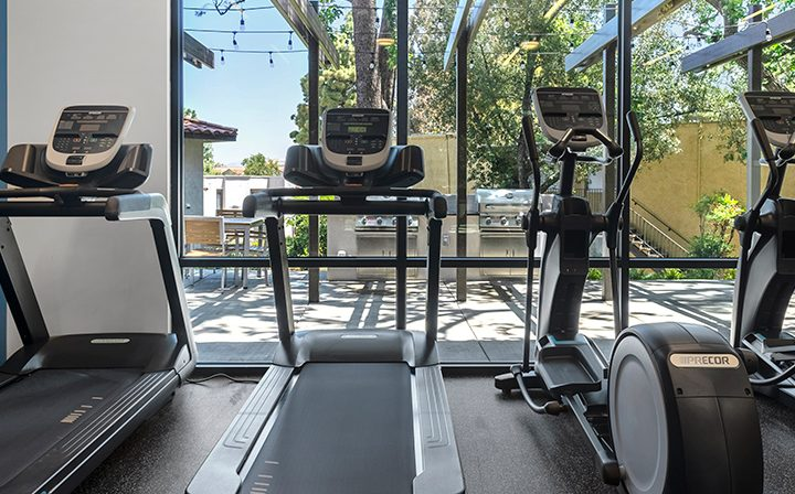 Treadmills facing the pool and BBQ area at the Thousand Oaks apartments community Los Robles