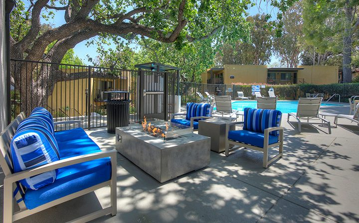 Lounge area with blue-padded chairs near pool at the Thousand Oaks apartments community Los Robles